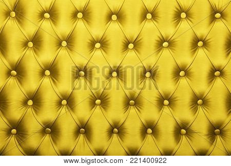 Yellow vivid capitone textile background, retro Chesterfield style checkered soft tufted fabric furniture diamond pattern decoration with buttons, close up