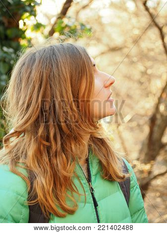 Outdoors close up profile portrait of pretty girl. Long hair. Sun coloring her in gols. Thoughtful expression. Trees and branches view at background