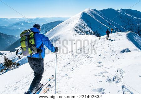 Skialpinists on snowy mountains, Symbol winter sports, Skialpinists group in european alps, , Group skialpinists in mountains, Concept winter adventure, Dangerous sport, Group of skiers on mountain top