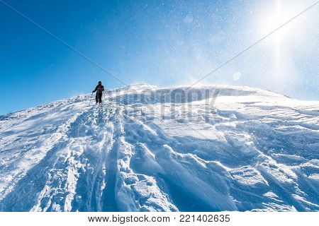 Young woman in snowy mountains with sun in field,  Woman on winter mountain, Female Tourist on walk european winter mountains