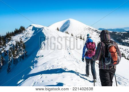 Women go on snowy mountain peak, Tourists in winter mountains, Girls walking on snowy mountains, Symbol winter experience, Background hiker in mountains