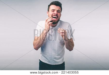 Teeth Problem. Man Feeling Tooth Pain. Closeup Of Bearded boy Suffering From Strong Tooth Pain. Attractive male Feeling Painful Toothache. Dental Health And Care Concept.