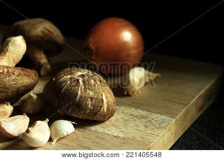 Fresh Mushroom with Garlic and Onion on Chopping Board