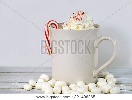 candy cane on white mug with hot cocoa drink and marshmallows on whitewashed wood