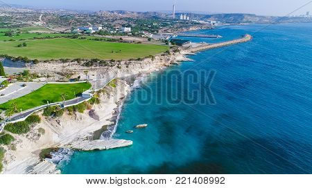 Aerial view of coastline and landmark big white chalk rock at Governor's beach, Limassol, Cyprus. The steep stone cliffs and deep blue sea waves crushing in coves and dark sand next to Kalymnos fish restaurant from above and vasilikos power station in the