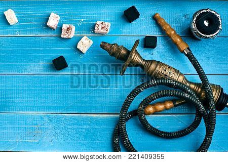 Tobacco background. Turkish smoking hookah with tobacco flavor of rahat lokum. Top view of a blue wooden background. Still life. Copy space. Flat lay