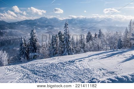 Mala Fatra mountains with Velky Rozsutec, Stoh and other hills from Velka Raca hill in Kysucke Beskydy mountains on slovakian - polish borders during freezing winter day with blue sky and clouds