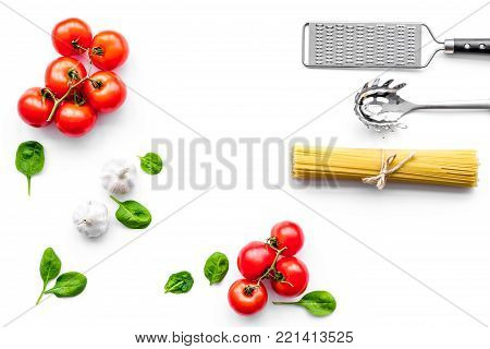 Preparing to cook pasta. Spaghetti, tomatoes, garlic, cheese grater, spoon for spaghetti on white background top view.