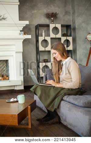 Happy Young Woman Using Laptop and Surfing the Web. Cute Student Girl at Home