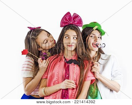 Three charming, cute, fashionable girls celebrating the holiday, holding a fake mustache and lips, isolated on white
