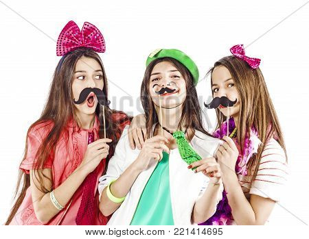 Three charming girls spend time on a new year or birthday. Holding a fake mustache and lips. Wearing masquerade hats.