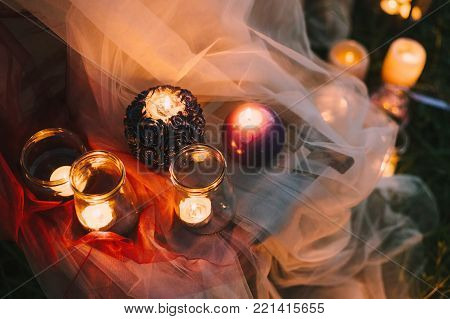 Night fine art rustic outdoor wedding details summer spring ceremony with decor burning lowlight candles standing table covered with veil soft cloth tulle pastel tones and on the grass Closeup view.