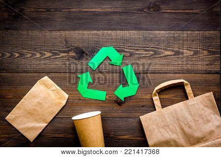 Green paper recycling sign among waste material paper on dark wooden background top view space for text.
