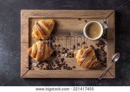 Fresh baked traditional croissants and mug of espresso coffee, coffee beans, sugar on wooden tray over black texture background. Top view, space
