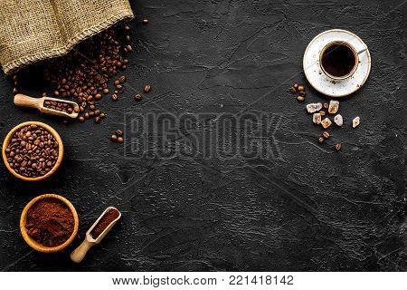Coffee concept. Roasted beans, ground coffee, cup of espresso and sugar on black background top view.