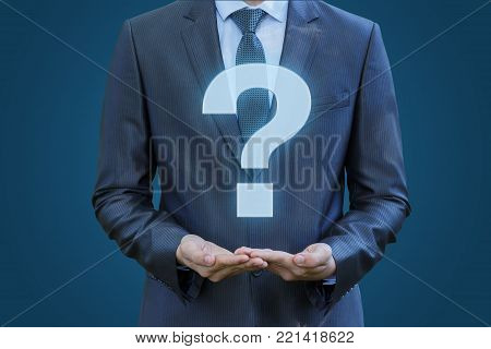Businessman showing a bigger question mark on a blue background. The answers to the questions.