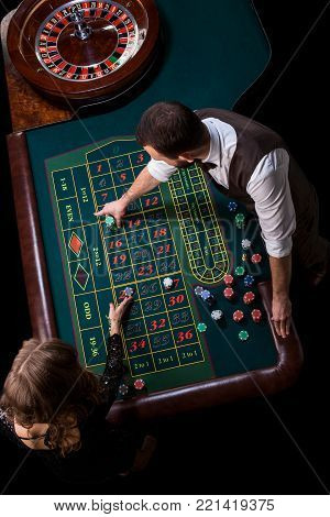 Croupier and woman player at a table in a casino. Picture of a classic casino roulette wheel. Gambling. Casino. Roulette. Poker. Top view of a green roulette table