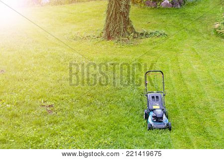 Mowing lawns. Lawn mower on green grass. mower grass equipment. mowing gardener care work tool close up view sunny day. Soft lighting
