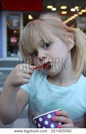 Little girl enjoys eating chocolate ice cream