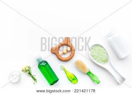 Soft bath cosmetics for kids with chamomile. Bottles, spa salt, tooth brush and toy on white background top view.