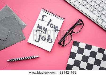 Find dream job. Handwritten motto I love my job in notebook on office desk on pink background top view.