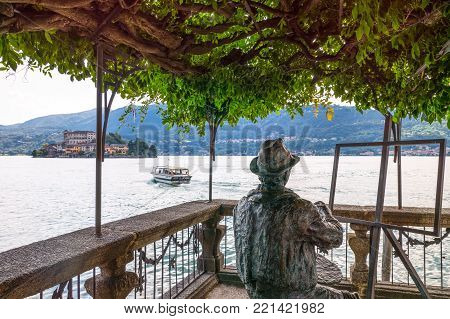 Orta San Giulio, Italy - August 18, 2013: A statue looking at the lake with San Giulio Island in the background