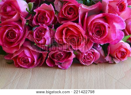 Bouquet of pink roses on wooden background.St Valentine's Day,Mother's Day or Happy Birthday concept with copy space.Pink roses bouquet.Selective focus.