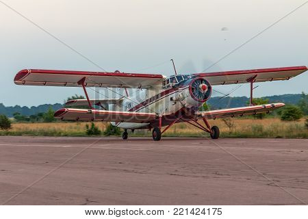 Zhitomir, Ukraine - June 18, 2011: Antonov An-2 biplane is taking off on sunset from the airstrip