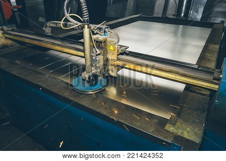 CNC programmable laser plasma cutting machine cuts sheet of metal, modern industrial metalwork technology, professional manufacturing equipment, toned poster