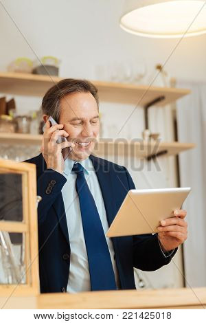 One specification. Busy occupied stylish man standing in the bright room looking at his tablet and holding the cellphone near his head.