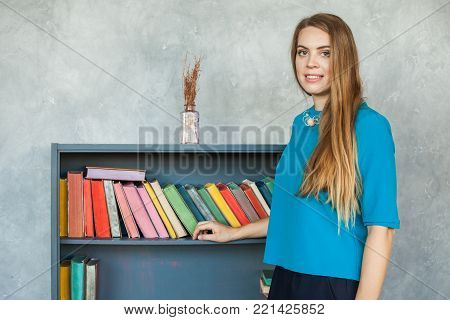 Student Girl on Bookshelves Background. Real People Portrait