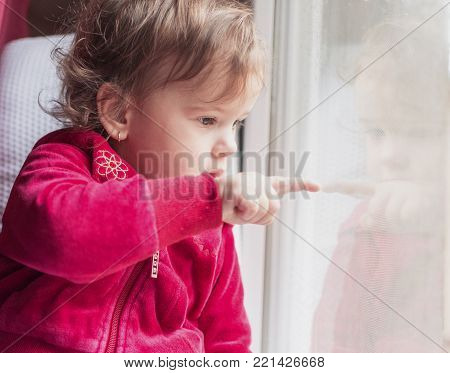 a little girl sits on the window and touches her reflection in the same with her finger