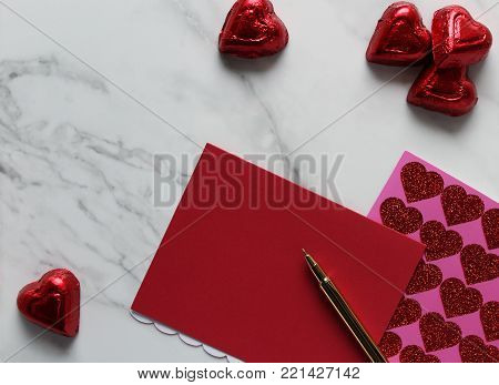 Valentine's stationary and candy with white marble copy space.