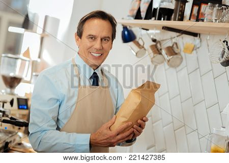 Best choice. Satisfied pleasant occupied man standing in the kitchen holding the pack and smiling.