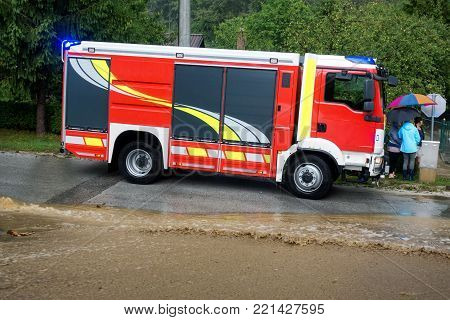 Red fire brigade engine, firefighting truck and firefighters rush to rescue when floods hit village in Europe after heavy rain, severe weather, rescue services