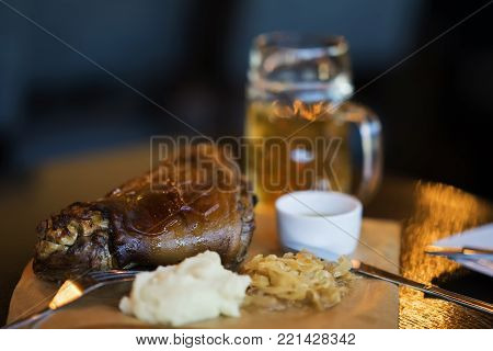 Pork shank with a traditional side dish to beer. Blurred background image. Real scene in bar or in pub. Concept of beer culture, Craft brewery, uniqueness of beer grades, meeting of low alcohol beverage lovers