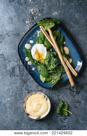 Poached egg on fresh spinach leaves with hollandaise sauce, salt and bread sticks served in blue square plate over blue texture background. Top view, space. Vegetarian healthy eating