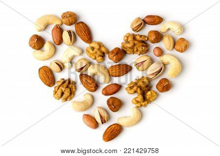 Heart of different nuts laid out on a white background, top view.. Walnut, hazelnut, peanut, cashew, almonds and pistachios