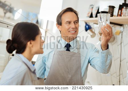 Incredibly purity. Interested senior satisfied man in a pinafore spending time with colleague smiling and overlooking the glass.