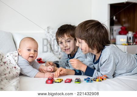 Three children, baby and his older brothers in bed in the morning, playing together, laughing and having a good time, sharing special moment, bonding