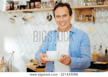 Take it please. Handsome pleasant polite man standing in the kitchen smiling and giving a cup of coffee.