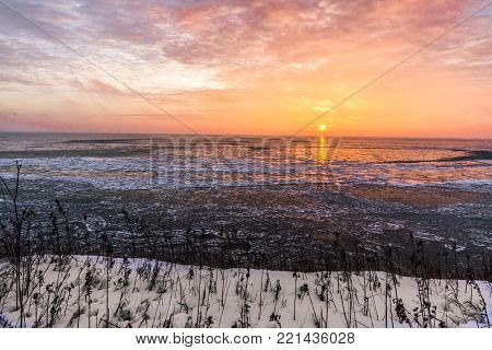 Frozen Great Lakes Sunrise. Scenic sunrise reflection over the icy Great Lakes horizon on the coast of Lake Huron from an overlook in Port Sanilac, Michigan