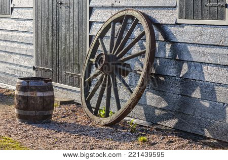 Image of a rusty old wheel and a barrel near a the wall of a barn.