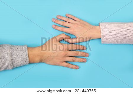 Women's hand goes to the man's hand on blue background.
