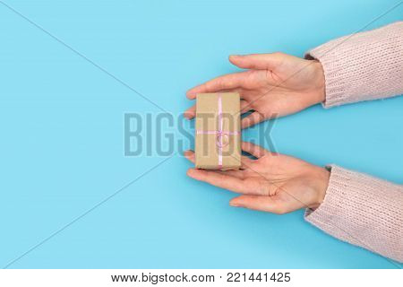 Women's hands hold a small gift on a blue background. Women's hand goes to the man's hand on blue background.