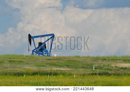 blue oil lease on the prairies against clouds
