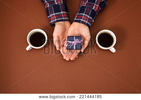 The male hands are closed on a brown background. The guy gives a gift to a girl. Men's hands next to two cups of coffee and with gift.
