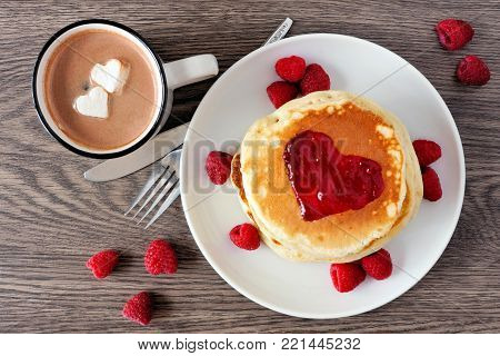Pancakes With Jam In Shape Of Heart, Hot Chocolate And Raspberries Over A Wood Background. Love Conc