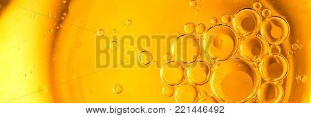 Yellow and orange bubbles, drops of oil in water, olive oil for cooking background.