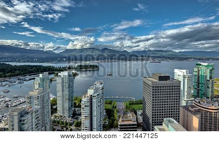 Aerial view at Vancouver Harbour,  Downtown of Vancouver City and North Vancouver on opposit side of Burrard Inlet  against the background of a mountain ridge and cloudy sky.